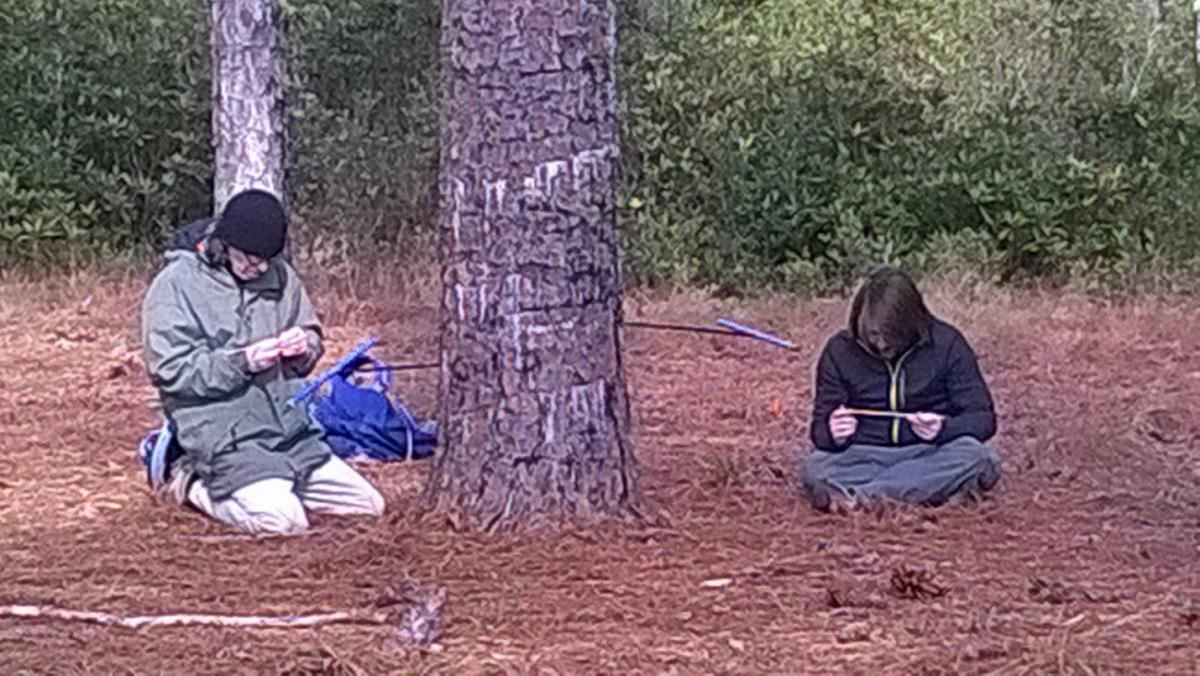 Dr. Knapp and Maxwell examining core samples they just obtained with increment borers (blue instrument) from a longleaf pine tree.